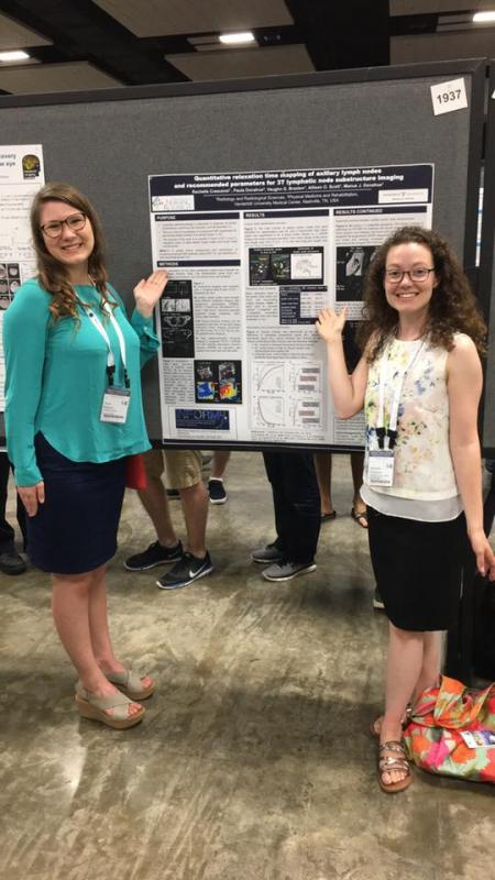 two people presenting a poster at ISMRM