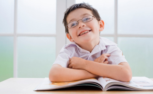 Photo of child with glasses and book.