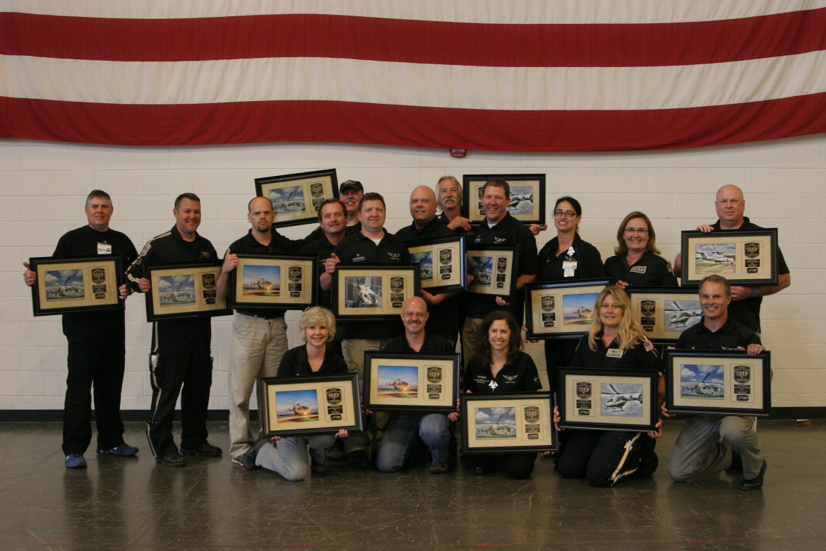 Some of those recognized for making or exceeding 1,000 patient flights are (left to right, front) Teresa Fulwood, Steve Wilkinson, Marcie Johnson, Erica Woodside, and Mark Tankersley. (Back) Tim Hurst, Tim Morman, Joe Brentise, Tony Smith, Chris Rediker, Greg Wamack, Danny Bridges, Lis Henley, Keela Dement, and John Kennedy. Not all crew members recognized are in the photo.