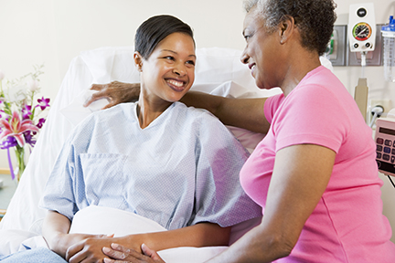 Mom visiting adult daughter in hospital bed, smiling