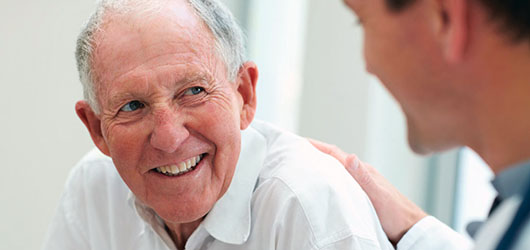 Smiling patient speaking with doctor